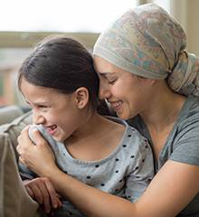 Woman with cancer hugging daughter